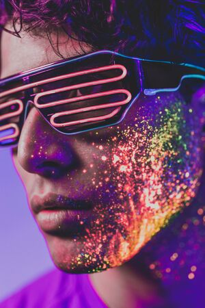 Handsome boy dancing at the rave party with fluorescent paintings on his face Stockfoto