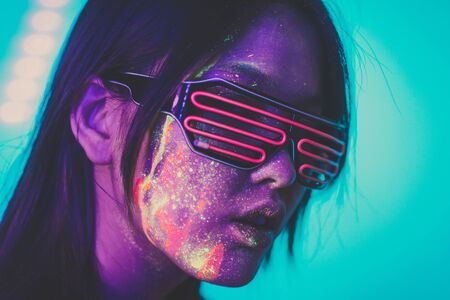 Beautiful young woman dancing and making party with fluorescent painting on her face. Neon facial portraits Stock Photo - 125903728