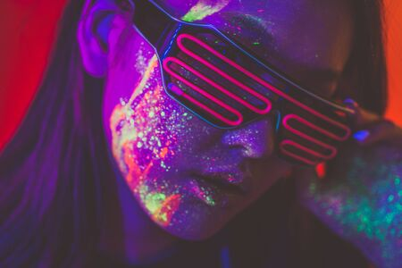 Beautiful young woman dancing and making party with fluorescent painting on her face. Neon facial portraits Stock Photo - 125903731