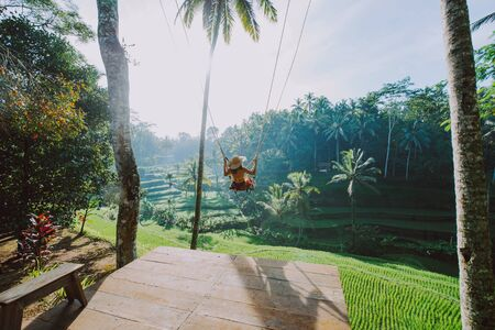 Beautiful girl visiting the Bali rice fields in tegalalang, ubud. Using a swing over the jungle. Concept about people, wanderlust traveling and tourism lifestyle Stok Fotoğraf - 125916345