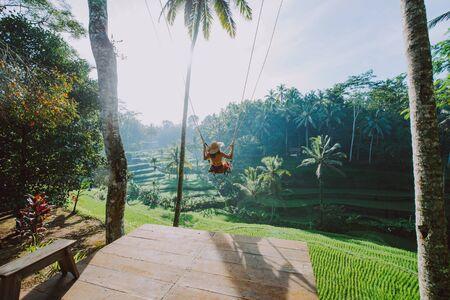 Schönes Mädchen, das die Bali-Reisfelder in Tegalalang, Ubud besucht. Mit einer Schaukel über den Dschungel. Konzept über Menschen, Fernweh Reisen und Tourismus-Lifestyle Standard-Bild