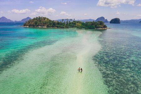 Profiter du temps passé à la plage. Les gens marchant sur le sable blanc, avec la jungle tropicale en arrière-plan. Concept sur les voyages et la nature