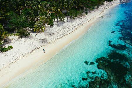 Mann steht am Strand und genießt den tropischen Ort mit Aussicht. karibische Meeresfarben und Palmen im Hintergrund. Konzept über Reisen und Lifestyle Standard-Bild