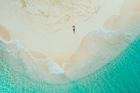 Daku island view from the sky. Man relaxing taking sunbath on the beach.shot taken with drone above the beautiful scene. concept about travel, nature, and marine landscapes Фото со стока