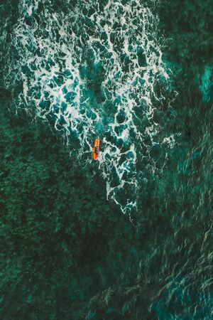 Aerial shot of surfers doing surf at sunset time. picture provided with drone. Concept about nature and sport Stok Fotoğraf