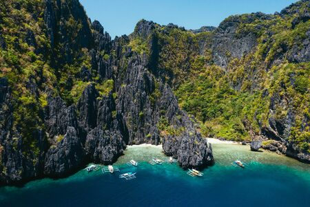 Small lagoon in El nido. People walking on the white sand, with tropical jungle in the background. Concept about traveling and nature