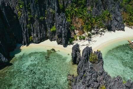 Small lagoon in El nido. People walking on the white sand, with tropical jungle in the background. Concept about traveling and nature 免版税图像