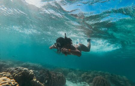 Beautiful woman swimming underwater in a tropical sea full of corals. under water shot with action camera. concept about wanderlust travels