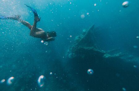 Discovering a japanese ship wreck from second world war. Beautiful woman swimming underwater in a tropical sea. under water shot with action camera. concept about wanderlust travels