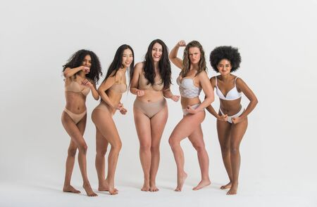 Grupo de mujeres con diferente cuerpo y etnia posando juntas para mostrar el poder y la fuerza de la mujer. Tipo de cuerpo femenino curvilíneo y delgado Foto de archivo