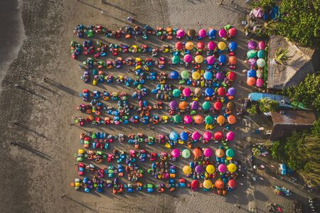 Aerial view of the beach with multicolored umbrellas and decks: