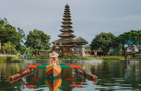 Beautiful girl kayaking on the catamaran at the ulun datu pura bratan temple, in Bali Standard-Bild