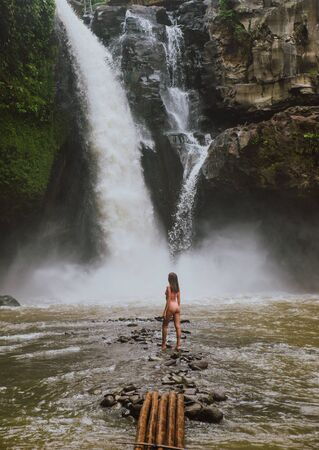 Beautiful girl having fun at the waterfalls in Bali. Concept about wanderlust traveling and wilderness culture
