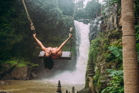 Beautiful girl having fun at the waterfalls in Bali. Concept about wanderlust traveling and wilderness culture 스톡 콘텐츠