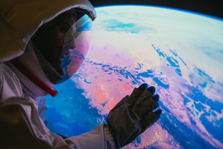 Astronaut looking planet earth from the window of his capsule. Concept about science and space exploration