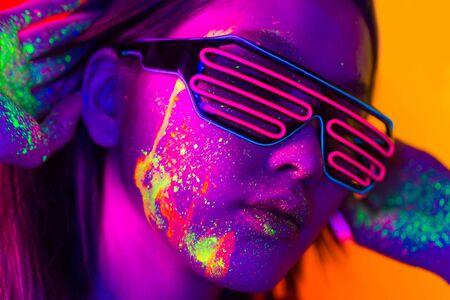 Portrait de femme à la mode avec peinture colorée sur le visage