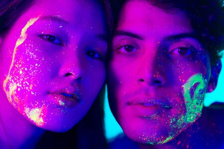 Portrait of fashionable man and woman with colored  painting on the face Stock Photo