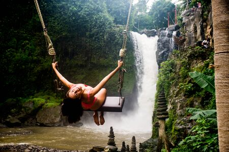 Beautiful young woman posing at the great Tegenungan waterfall in the deep rainforest of Bali island, Indonesia. 写真素材