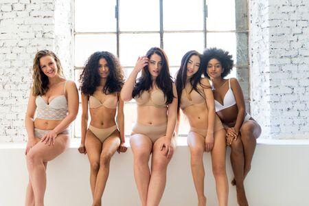 Multiethnische Gruppe schöner Frauen, die in Unterwäsche in einem Schönheitsstudio posieren