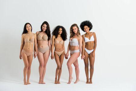 Grupo multiétnico de hermosas mujeres posando en ropa interior en un estudio de belleza: modelos de moda multiculturales que muestran sus hermosos cuerpos tal como son, conceptos sobre belleza, aceptación y diversidad.