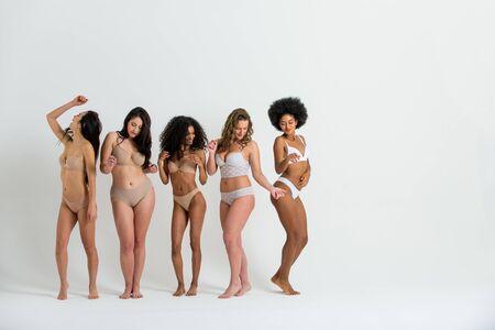 Multiethnische Gruppe schöner Frauen, die in Unterwäsche in einem Schönheitsstudio posieren - Multikulturelle Models, die ihre schönen Körper so zeigen, wie sie sind, Konzepte über Schönheit, Akzeptanz und Vielfalt