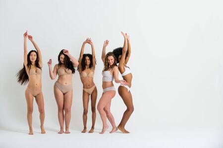 Grupo multiétnico de hermosas mujeres posando en ropa interior en un estudio de belleza: modelos de moda multiculturales que muestran sus hermosos cuerpos tal como son, conceptos sobre belleza, aceptación y diversidad. Foto de archivo