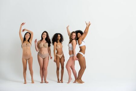Multi-ethnic group of beautiful women posing in underwear in a beauty studio - Multicultural fashion models showing their beautiful bodies as they are, concepts about beauty, acceptance and diversity Stock Photo