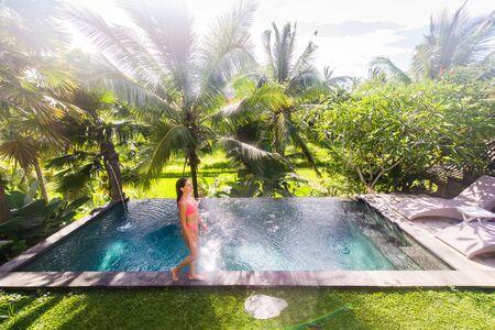Beautiful woman in bikini relaxing in a outdoor swimming pool in a Bali luxury resort