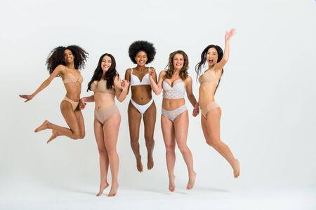 Multi-ethnic group of beautiful women posing in underwear in a beauty studio Stockfoto - 127313471