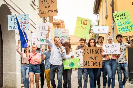 Group of activists is protesting outdoors - Crowd demonstrating against global warming and plastic pollution, concepts about green ecology and environmental sustainability
