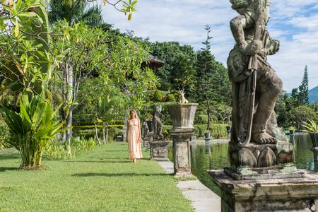 Young beautiful woman in Taman Ujung water palace, Bali island, Indonesia