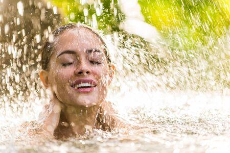 Bella donna in bikini che si rilassa in una piscina all'aperto in un resort di lusso di Bali Archivio Fotografico