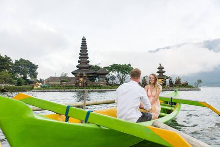 Young beautiful couple paddling on a wooden boat at Pura Ulun Danu Bratan, Bali - Tourists exploring Bali