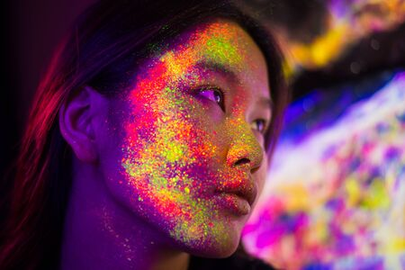 Portrait of fashionable woman with colored fluo painting on the face Stock Photo