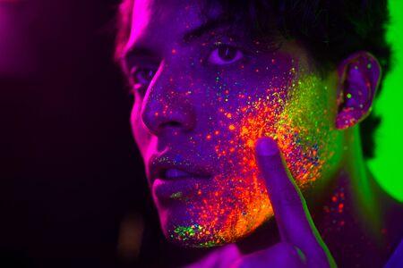 Portret van modieuze man met gekleurd schilderij op het gezicht