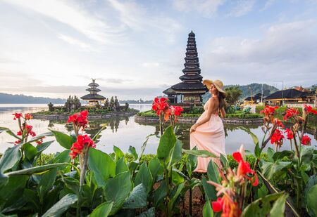 Young woman  at the Pura Ulun Danu Bratan, Bali. Hindu temple surrounded by flowers on Bratan lake, Bali.