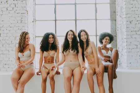 Multiethnische Gruppe schöner Frauen, die in Unterwäsche in einem Schönheitsstudio posieren Standard-Bild