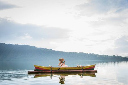 Young woman traveler paddling on a wooden boat at Pura Ulun Danu Bratan, Bali.