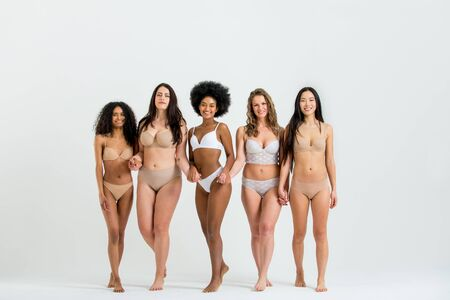 Multi-ethnic group of beautiful women posing in underwear in a beauty studio