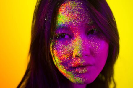 Portrait of fashionable woman with colored fluo painting on the face - Fashion model on colored background