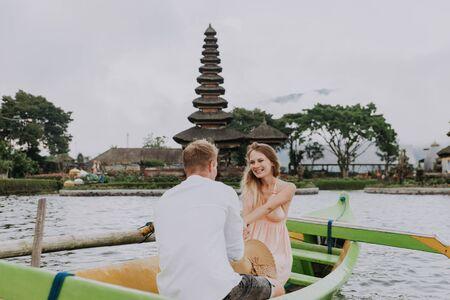 Young beautiful couple paddling on a wooden boat at Pura Ulun Danu Bratan, Bali - Tourists exploring Bali