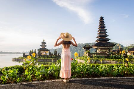 Young woman at the Pura Ulun Danu Bratan, Bali. Hindu temple surrounded by flowers on Bratan lake, Bali.