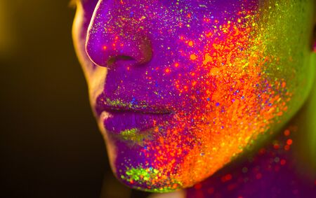 Portrait of fashionable man with colored fluo painting on the face - Fashion model on colored background