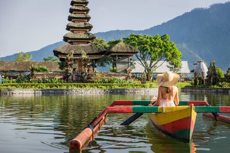 Young woman traveler paddling on a wooden boat at Pura Ulun Danu Bratan, Bali.