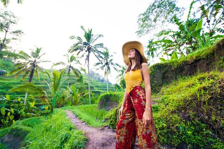 Young woman on green cascade rice field plantation at Tegalalang terrace.