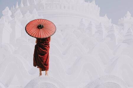 Monk standing on white temple Stock Photo
