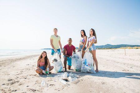 Gruppe von Aktivistenfreunden, die Plastikmüll am Strand sammeln. Leute säubern den Strand mit Taschen. Konzept über Umweltschutz und Meeresverschmutzungsprobleme Standard-Bild
