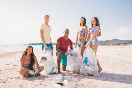 Group of activists friends collecting plastic waste on the beach. People cleaning the beach up, with bags. Concept about environmental conservation and ocean pollution problems Foto de archivo