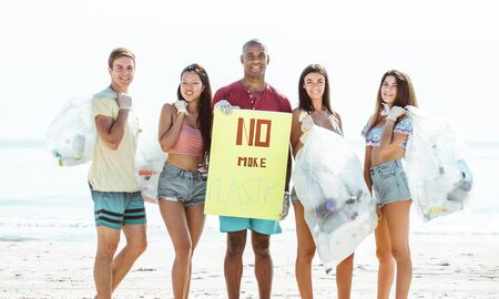 Group of activists friends collecting plastic waste on the beach. People cleaning the beach up, with bags. Concept about environmental conservation and ocean pollution problems Stock Photo