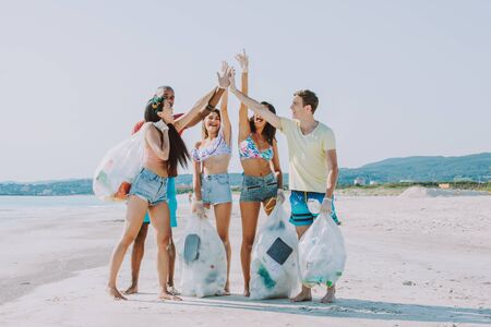 Group of activists friends collecting plastic waste on the beach. People cleaning the beach up, with bags. Concept about environmental conservation and ocean pollution problems Banque d'images